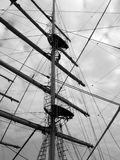 Tall Ship Mast and Rigging. Silhouette of a Tall Ship's mast against a cloudy sky, with a crewmember climbing to the crows nest Royalty Free Stock Image
