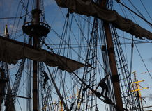 Tall ship masts and rigging silhouetted against a dramatic sky at sunset. With men working Stock Images