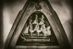 Tall ship model in triangular wooden frame, anchor,rope, isolated on blurred background, faded in sepia style photography royalty free stock photo