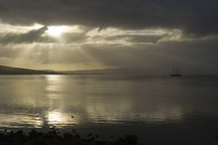 Tall ship morning. A tall ship is moored in a calm sea lit by sunbeams at Rothesay Bay, Bute, Scotland royalty free stock photography