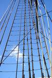 Tall Ship Rigging Ropes over Blue Sky. Tall sail ship rigging ropes and shroud over blue sky Royalty Free Stock Images