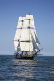 Tall ship sailing on blue water. A tall ship flying the American flag sails on blue waters with cannons firing stock images