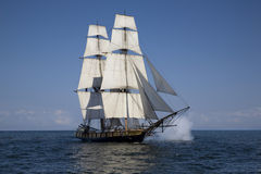 Tall ship sailing on blue water. A tall ship flying the American flag sails on blue waters with cannons firing Royalty Free Stock Photo