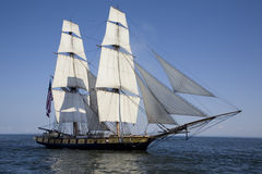 Tall ship sailing on blue water. A tall ship flying the American flag sails on blue waters Royalty Free Stock Photos