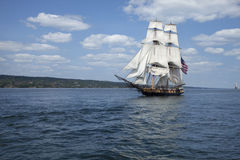 Tall ship sailing on blue water. A tall ship flying the American flag sails on blue waters stock image