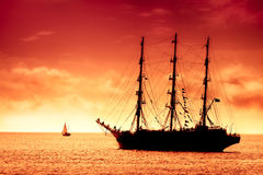 Tall ship sailing in red. Large black tall  ship on the high seas at dusk. Flying Dutchman at the amber red sunset Stock Photography