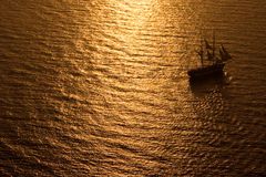 Tall Ship Sailing into Sunset. A ship sailing into the dramatic sunset in Santorini, Greece Stock Photography