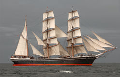 Tall Ship at Sea. Vintage windjammer tall ship with full sails against a dark gray sky and sea royalty free stock photos