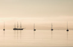 Tall Ship Silhouette Calm Waters. Tall ship silhouette on calm waters of Loch Scresort, Rum, Scotland Stock Photos