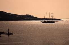 Tall ship silhouetted at sunset at Santorini. Beautiful dreamy tranquil sunset or sunrise with a four-masted tall ship silhouetted against the calm water of the royalty free stock photography
