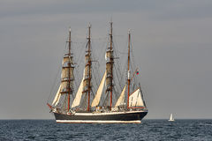 Tall Ship under sail with the shore in the background Stock Photography