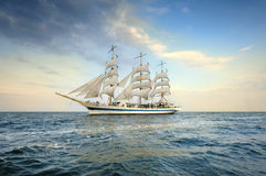 Tall Ship under sail with the shore in the background Stock Image