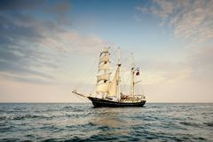 Tall Ship under sail with the shore in the background Stock Images