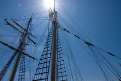 Tall ships. Looking up at the masts of a tall sailing ship into the sun Stock Photo
