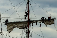 Tall Ships Learning the Ropes. Lacing on one of the top sails of and old sailing ship Royalty Free Stock Photography