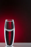Tall shot glass. Curved tall shot glass off centre on a deep red background Royalty Free Stock Images