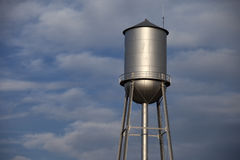 Tall silver water tower in front of a cloudy blue  Royalty Free Stock Photos