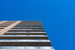 Tall skyscraper building wall with blue sky on the background Stock Photography