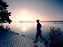 Tall slim man is running along lake in park in sunny daybreak. royalty free stock image