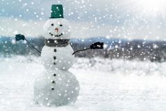 Tall smiling snowman with green bucket hat, scarf and gloves on tree branch hands on white snowy winter landscape, big snowflakes royalty free stock image