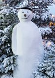 Tall snowman with hat in front of snow covered trees at night. Tall Snowman with hat and smile in front of snow covered trees at night Stock Photography