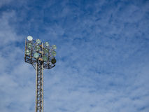 Tall spotlights tower at sports stadium. Old and tall spotlights tower with 12 bulbs at sports stadium in the morning/afternoon. The background is blue sky with Royalty Free Stock Photo
