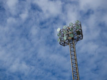 Tall spotlights tower with at sports stadium. Old and tall spotlights tower with 12 bulbs at sports stadium in the morning/afternoon. The background is blue sky Stock Image