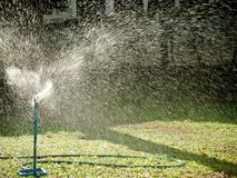 Tall sprinkler watering the lawn with morning sunlight. royalty free stock photos