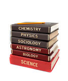 Tall stack of books. Tall stack of different university level science textbooks like chemistry, physics, and astronomy  on a white background Royalty Free Stock Photography