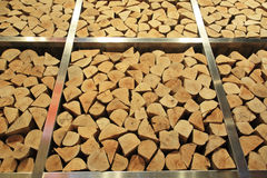 Tall stack of firewood logs on iron storage Stock Photos