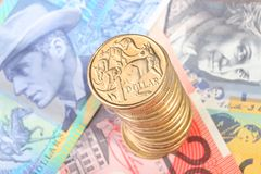 Stack of Australian dollar coins. A tall stack of gold Australian one dollar coins sits on top of three Australian bank notes Royalty Free Stock Photo