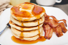 Tall stack of pancakes with bacon. A tall stack of pancakes with butter and dripping syrup and three strips of bacon Stock Photography