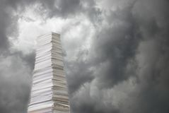 Stack of paper against a stormy sky. Tall stack of paper against a background of stormy sky covered with dark clouds stock images