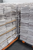 Tall stacks of newspapers on pallets Stock Photo