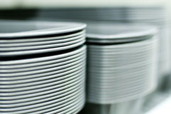 Tall Stacks of White Plates. Several tall stacks of white plates on a shelf Royalty Free Stock Image