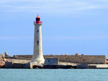 Stone lighthouse on breakwater. The tall stone lighthouse on the breakwater at the port of Sete in the south of France stock photo