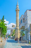 The tall stone minaret. ANTALYA, TURKEY - MAY 6, 2017: The tall stone minaret of Tekeli Mehmet Pasa Mosque and the Clock Tower on the background, on May 6 in royalty free stock photos