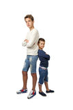 Tall teenager and little boy stand back to back Royalty Free Stock Photography
