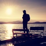 Tall tourist with backpack walk on beach at pedal boat in the sunset. Autumn at sea Stock Images