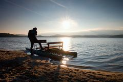 Tall tourist with backpack walk on beach at pedal boat in the sunset. Autumn at sea Royalty Free Stock Photo