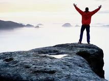 Tall tourist celebrate on the peak of the world . Orange thick fog bellow in deep valley. Dreamy daybreak Stock Images