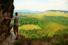 Tall tourist climbing on sharp cliff and  overlooking beautiful view above forest valley bellow. Stock Image