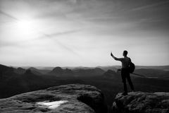 Tall tourist at dangerous cliff edge is taking selfie. On peak above valley. Mountain peak and deep valley with sun in the frame Royalty Free Stock Images