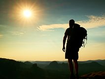 Tall tourist with poles in hand. Sunny evening in rocky mountains. Hiker with big backpack stand on rocky view point above misty v Royalty Free Stock Photo