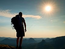 Tall tourist with poles in hand. Sunny evening in rocky mountains. Hiker with big backpack stand on rocky view point above misty v Royalty Free Stock Images