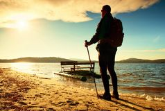 Tall tourist walk on beach at paddle boat in the sunset Stock Image