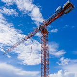 Tall tower crane over construction site with blue sky and clouds behind royalty free stock photos