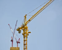 Tall tower cranes on construction site. Stock Photos