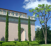 Tall Trees. Three Italian cypress trees stand tall in front of a pink Mediterranean type building surrounded by tropical landscaping stock photo