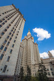 Tall university building with arrows of windows and golden spire under cloudy blue sky Stock Image